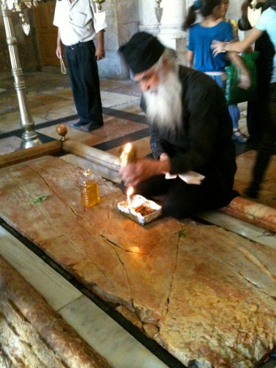 Orthodox priest anointing the stone where Jesus' body was laid with spices and oils